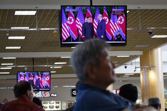 """""""Scanpix""""/AP nuotr./Singapūriečiai stebi Kim Jong Uno ir Donaldo Trumpo susitikimą"""