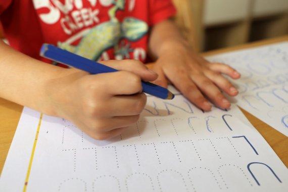 123RF.com nuotr./Vaikas mokosi rašyti