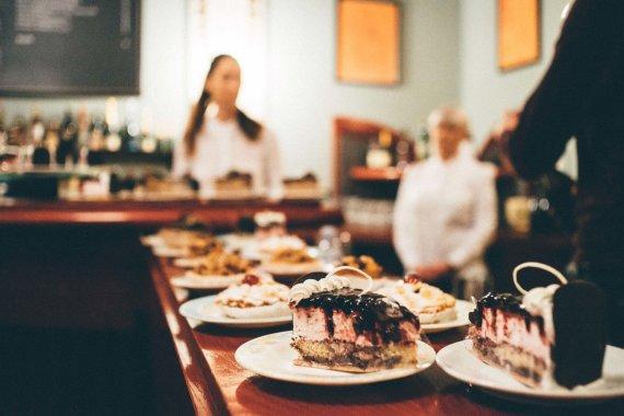 """Igno Nefo nuotr./Ant baro išdėlioti torto gabalėliai ir pyragėliai, pagaminti """"Stiklių"""" konditerijoje"""