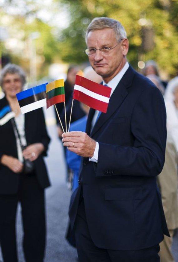 """AFP/""""Scanpix"""" nuotr./Švedijos užsienio reikalų ministras Carlas Bildtas laiko Baltijos šalių vėliavėles"""