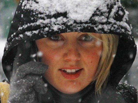 """""""Reuters""""/""""Scanpix"""" nuotr./Mergina šneka telefonu žiemą"""