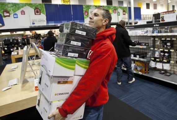 """""""Reuters""""/""""Scanpix"""" nuotr./Vyras neša išsirinktas elektronikos prekes"""