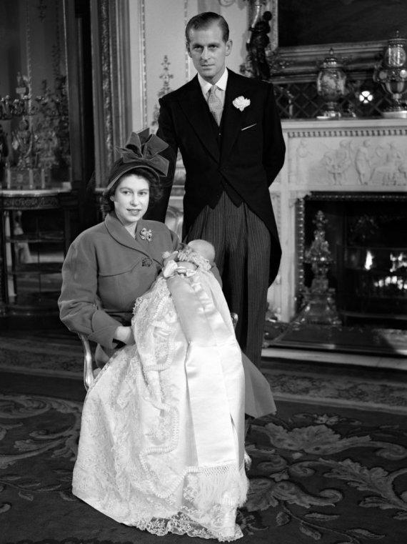 """Scanpix""/""PA Wire""/""Press Association Images"" nuotr./Karalienė Elizabeth II ir princas Philipas su sūnumi Charlesu per jo krikštynas (1948 m.)"