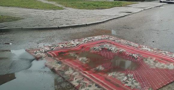 Mažeikių gyventojai kyla į kovą su duobėmis: dengia jas kilimais
