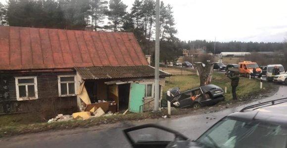Prie Karmėlavos kapinių susidūrė automobiliai: VW per avarijąįlėkė į namą