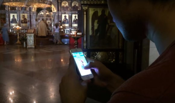 """Kadras iš """"YouTube""""/Ruslanas Sokolovskis gaudo pokemonus cerkvėje"""