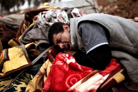 """AFP/""""Scanpix"""" nuotr./Artimieji gedi per antskrydį žuvusių aukų"""