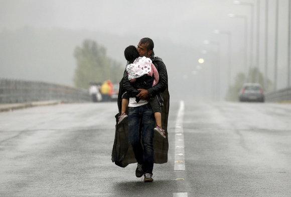"""""""Reuters""""/""""Scanpix"""" nuotr./Pabėgėlis iš Sirijos su vaiku Makedonijoje"""