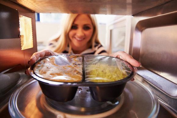 Fotolia nuotr./Moteris šildo maistą mikrobangų krosnelėje