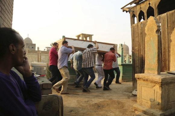 """""""Reuters""""/""""Scanpix"""" nuotr./Mirusiųjų miesto gyventojas stebi laidotuvių procesiją."""