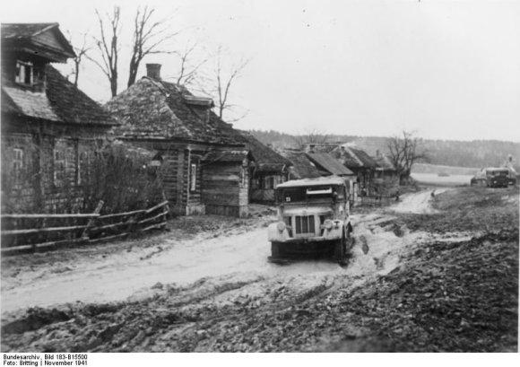Vokietijos Bundesarchyvo/Wikimedia.org nuotr./Klampyne virtęs kelias Rusijos kaime (1941 m. lapkritis)