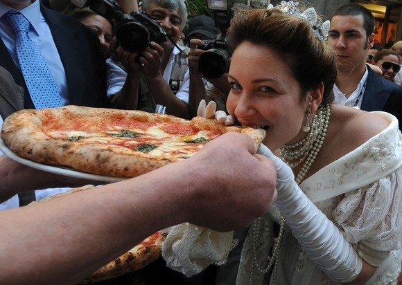 """AFP/""""Scanpix"""" nuotr./Aktorė apsirengusi kaip karalienė ragauja picą"""