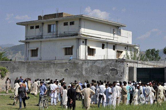 """AFP/""""Scanpix"""" nuotr./Vietos gyventojai ir žurnalistai šalia stovyklos, kurioje buvo nukautas Osama bin Ladenas"""