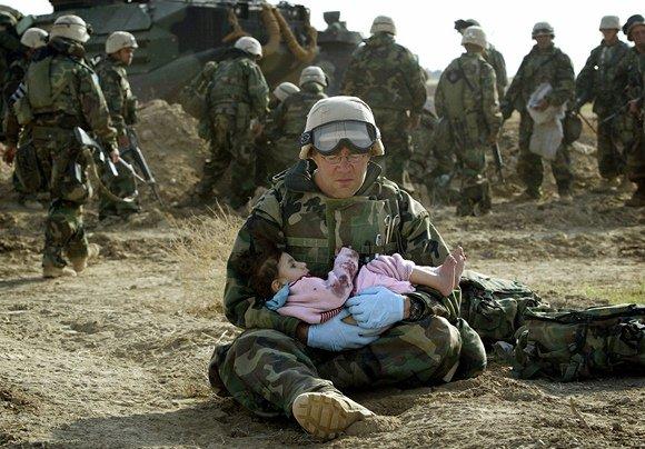 """""""Reuters""""/""""Scanpix"""" nuotr./JAV karys laiko irakiečių vaiką."""