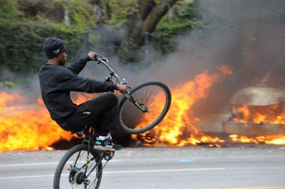 """""""Scanpix""""/AP nuotr./Dviratininkas netoli degančio policijos automobilio"""
