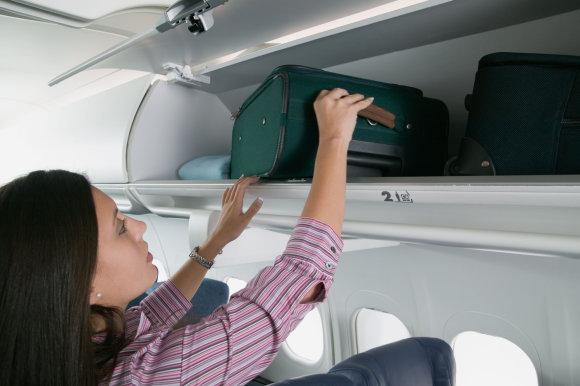 Vida Press nuotr./Moteris kelia savo rankinį bagažą