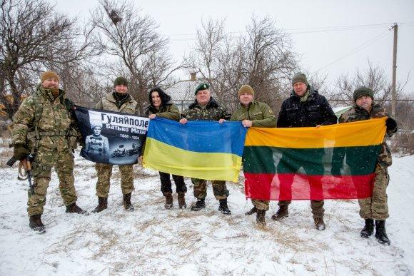 Vidmanto Balkūno / 15min nuotr./Lietuvos ir Ukrainos savanoriai suteikę paramą Ukrainos jūrų pėstininkams pozuoja su vėliavomis