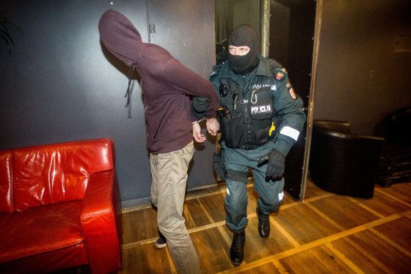 Vidmanto Balkūno / 15min nuotr./Policijos pareigūnas išveda sulaikytą klubo lankytoją