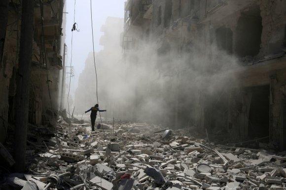 """""""Reuters""""/""""Scanpix"""" nuotr./Vyras vaikšto tarp griuvėsių Alepo mieste Sirijoje"""