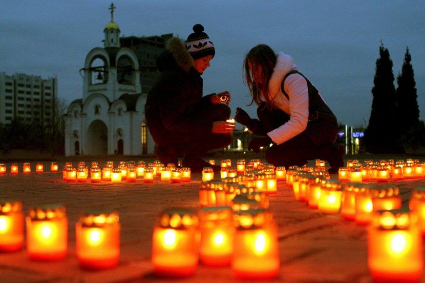 Žmonės dega žvakes netoli stačiatikių bažnyčios Minske