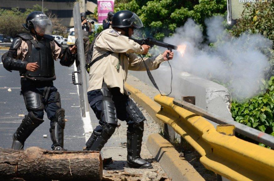 Venesuelos nacionalinės gvardijos kariai šaudo ašarines dujas į protestuotojus Karakase