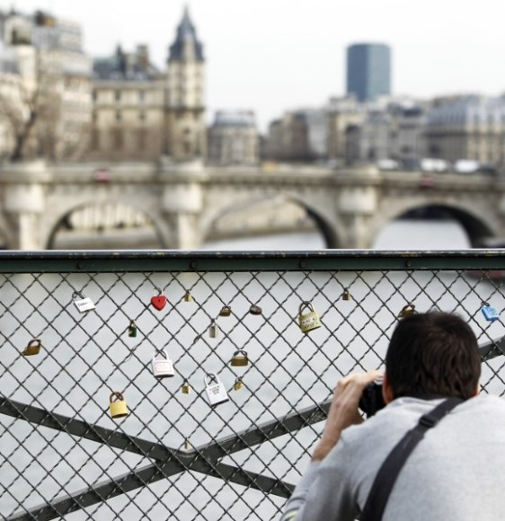 Turistas fotografuoja spynas ant Pont des Arts tilto turėklų.