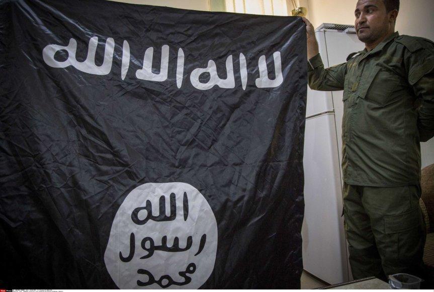 """Kurdų karys laiko po mūšių su džiahadistais paimtą """"Islamo valstybės"""" vėliavą"""