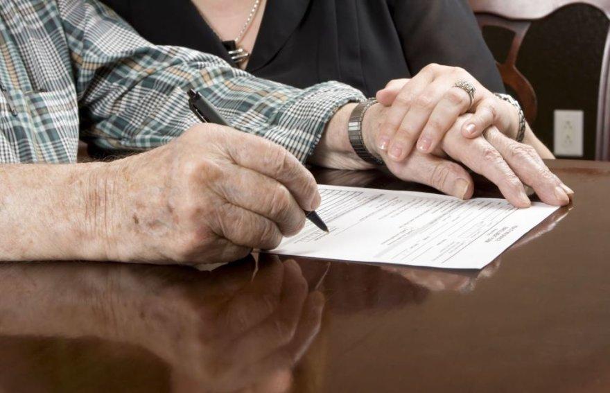 Pagyvenęs žmogus pasirašo sutartį