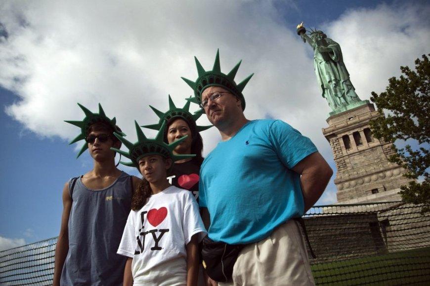 Šeima fotografuojasi prie Laisvės statulos