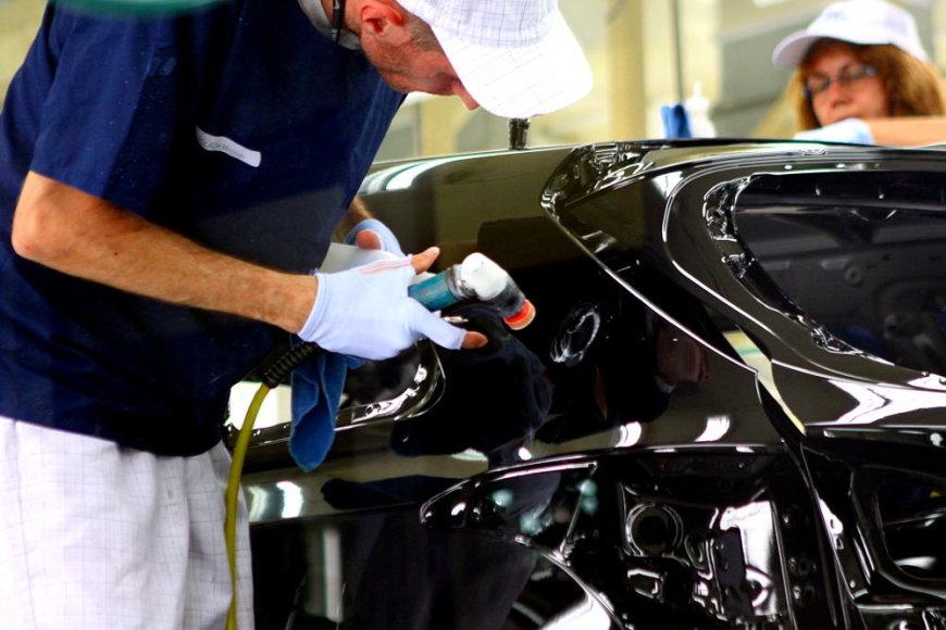 Darbuotojas poliruoja įbrėžimus po dažymo