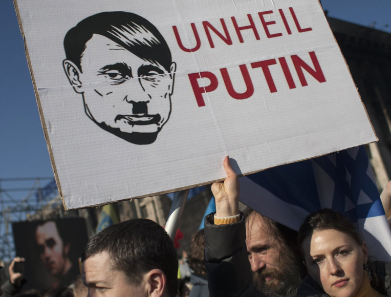 A woman holds a sign depicting Russian President Vladimir Putin as Adolf Hitler as she attends a rally at Independence Square in Kiev March 9, 2014. Russian forces tightened their grip on Crimea on Sunday despite a U.S. warning to Moscow that annexing the southern Ukrainian region would close the do