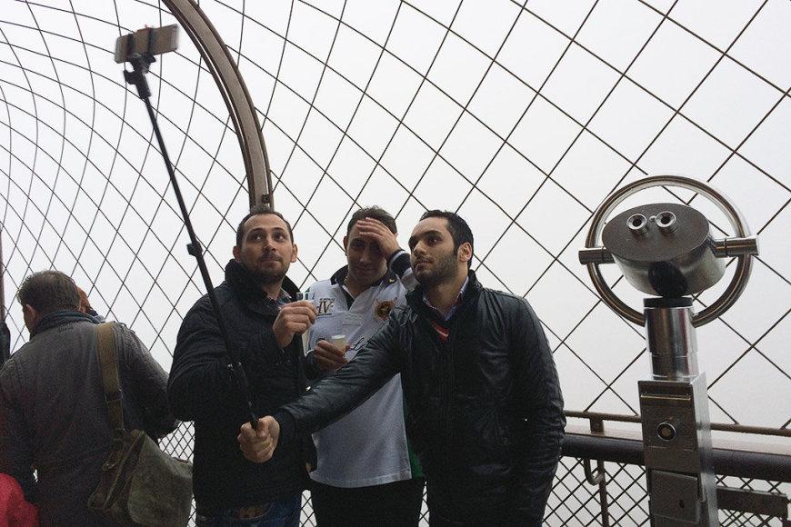 Turistai Paryžiuje darosi asmenukę su lazda