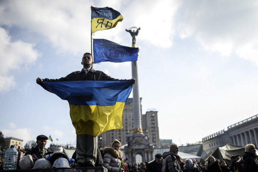 "A man holds a Ukrainian flag as he stands on Kiev's Independence Square on February 24, 2014. Ukraine issued an arrest warrant Monday for ousted president Viktor Yanukovych over the ""mass murder"" of protesters and appealed for $35 billion in Western aid to pull the crisis-hit country from the brink"