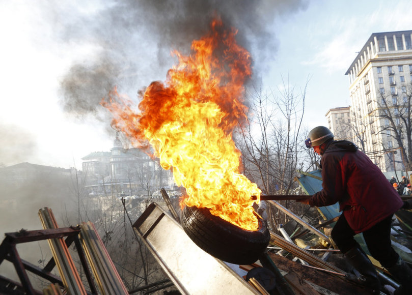 An anti-government protester moves a burning tyre at a barricade in Kiev February 21, 2014. Violence flared again in Kiev on Friday as Ukraine's opposition politicians pondered a draft deal with Russian-backed President Viktor Yanukovich which EU foreign ministers brokered to resolve the country's p