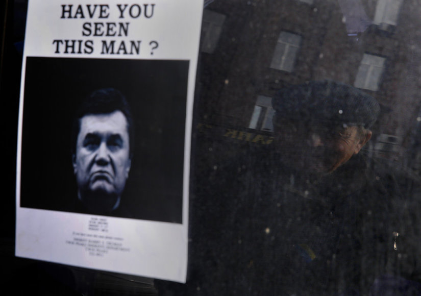 """A elderly man looks at a """"Wanted"""" notice for fugitive Ukrainian President Victor Yanukovich, plastered on the window of a car used as barricade near Kiev's Independent Square February 24, 2014. Ukrainian President Viktor Yanukovich, ousted after bloody street protests in which demonstrators were sho"""