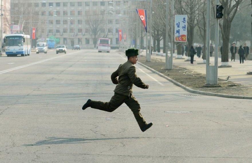 Šiaurės Korėjos karys bėga per gatvę.