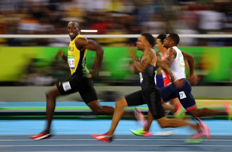 Usainas Boltas olimpinių žaidynių bėgimo rungtyje žvilgteli į nuo jo atsiliekančius varžovus