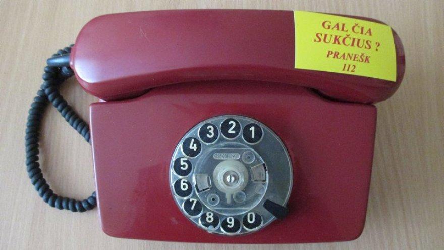 Telefonas su ryškiu lipduku, įspėjančiu apie pavojų