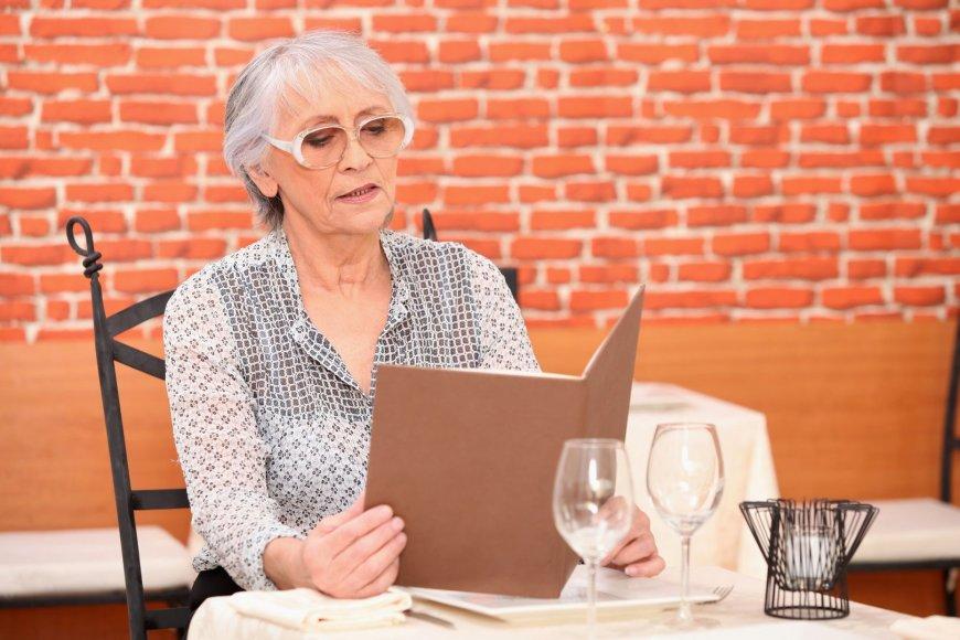 Moteris restorane skaito valgiaraštį