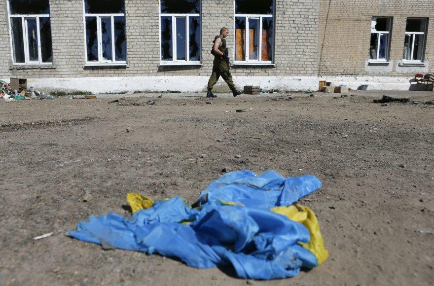 Prorusiškas teroristas eina netoli ant žemės gulinčios Ukrainos vėliavos