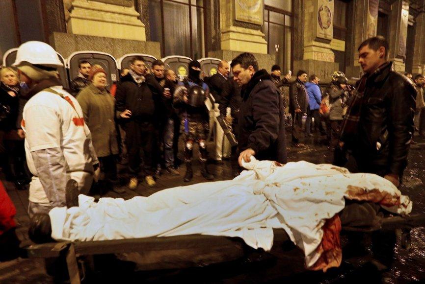Tėvas laiko savo žuvusio sunaus ranką, kurio gyvybė užgeso per protestus Kijeve