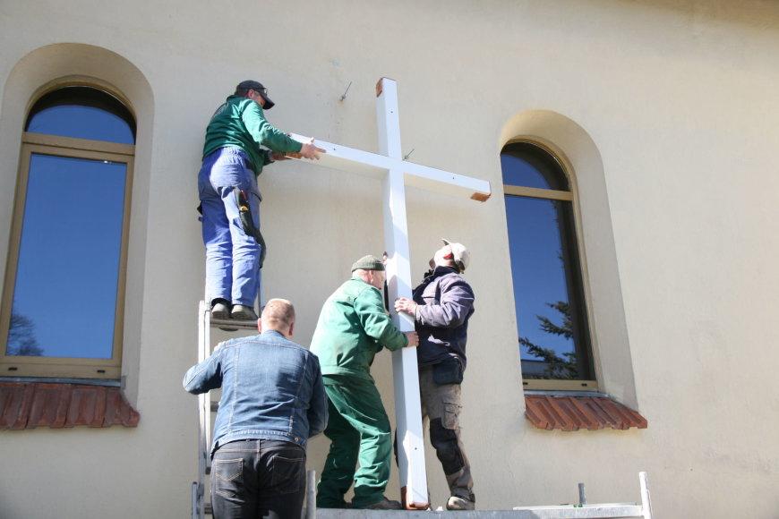 Prie bažnyčios tvirtinamas kryžius