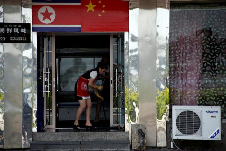 Padavėja iš Šiaurės Korėjos šluoja grindis Dandonge įsikūrusioje kavinėje