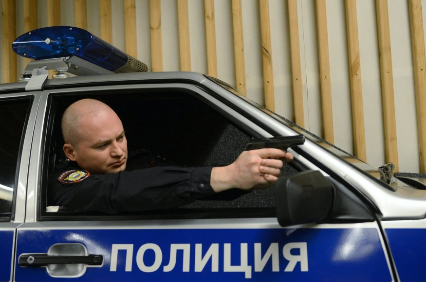 Rusijos policininkas automobilyje su ginklu