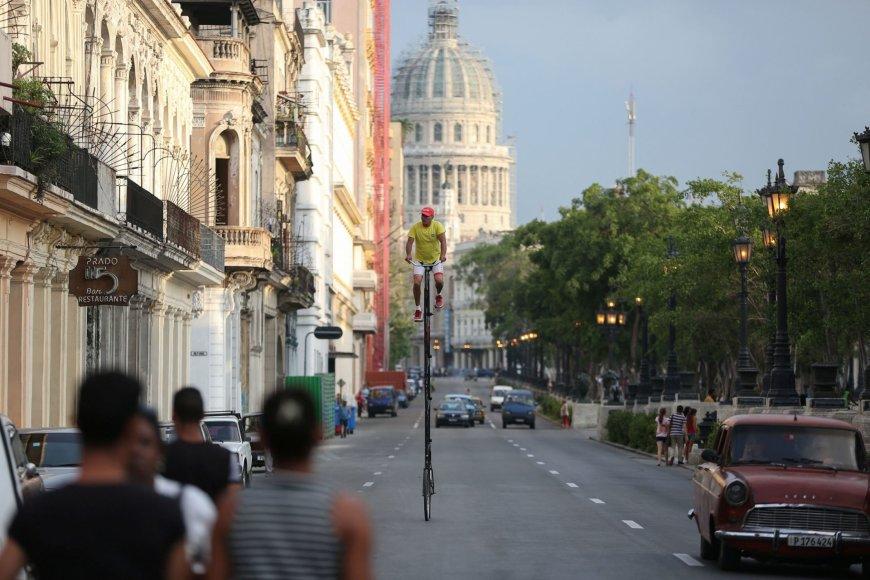"""""""Reuters""""/""""Scanpix"""" nuotr./Felixas Kuboje užsidirba pragyvenimui važinėdamas savadarbiais aukštais dviračiais su reklamomis"""