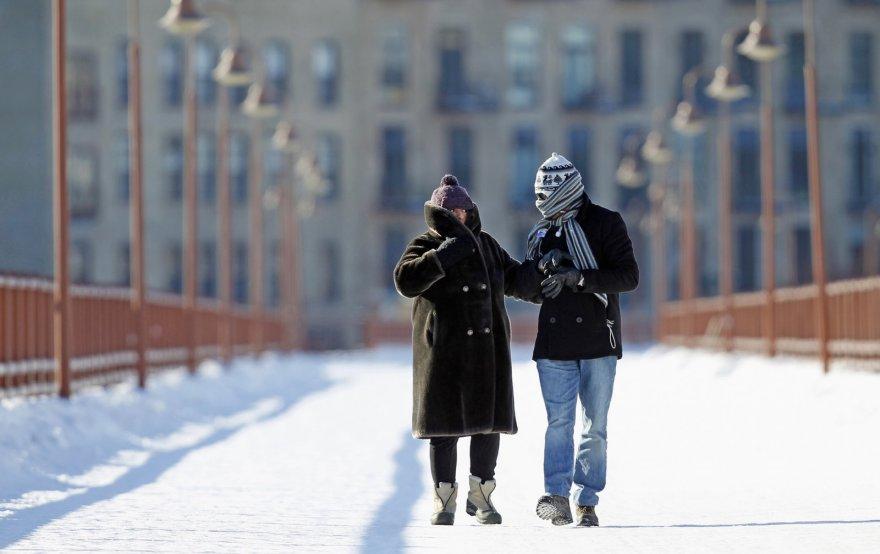 Nuo šalčio veidus užsidengę žmonės Mineapolyje