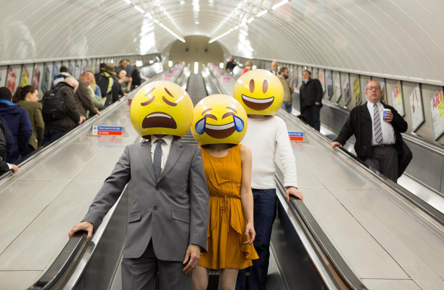 Žmonės su emoji šypsenėlių kaukėmis