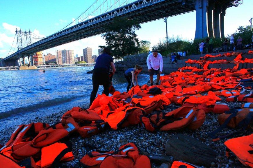Niujorke migrantų gynėjai Rytų upės pakrantėje išdėliojo daugybę gelbėjimo liemenių pabėgėlių krizei atspindėti.