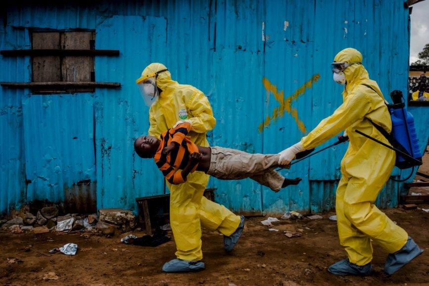 Balandžio 20 diena. Darbinikai neša berniuką, kuris kaip įtariama, užsikrėtęs ebola, į gydymo centrą Liberijoje