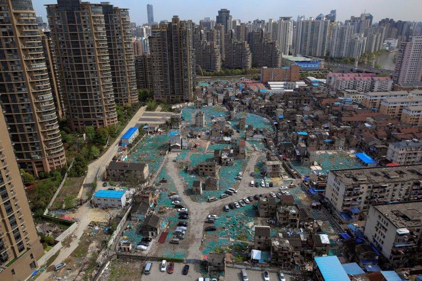 Ant aukso vertės žemės Šanchajuje gyvenantys kinai nesutinka atiduoti savo namų pusvelčiui